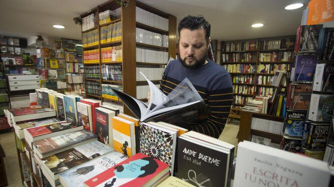 Un dependiente hojea un libro en Saltés (calle Ciudad de Aracena), librería de referencia en la capital onubense desde hace cuatro décadas.