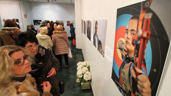 Dos mujeres observan el retrato realizado a Leyre Fernández Infante, campeona de España de tiro con arco, durante la inauguración de ayer en la Fundación Caja Rural del Sur.