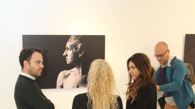 La fotógrafa Juana María Martín, de espaldas, ante su autorretrato, con la vicerrectora Joaquina Castillo y el técnico de Cultura Daniel Mantero.