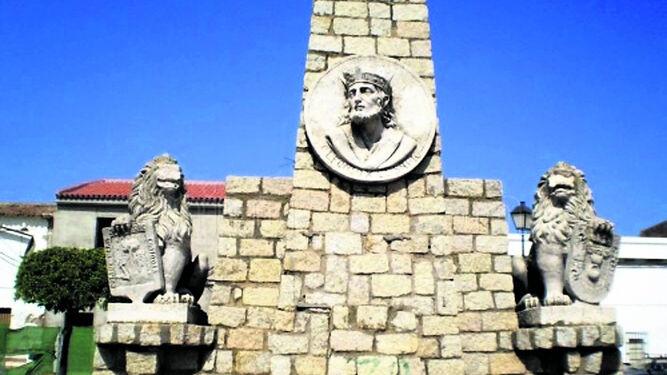 Turistas visitan las murallas de Niebla. Abajo, el desaparecido monumento a Alfonso X El Sabio, aún pendiente de su recuperación.