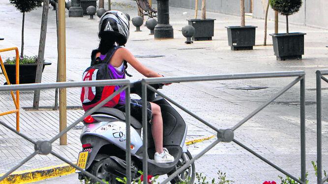 Una chica conduce un ciclomotor.