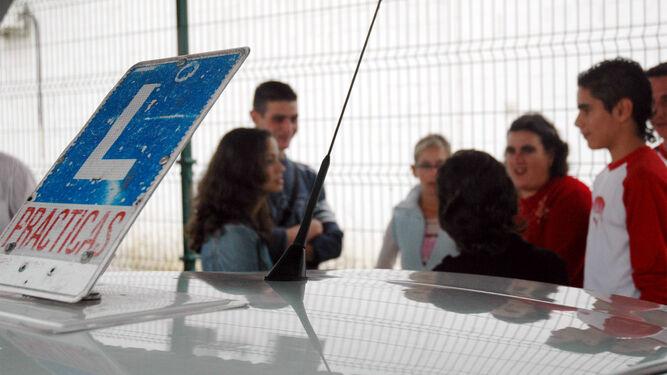 Un grupo de alumnos de una autoescuela charlan con su profesora.