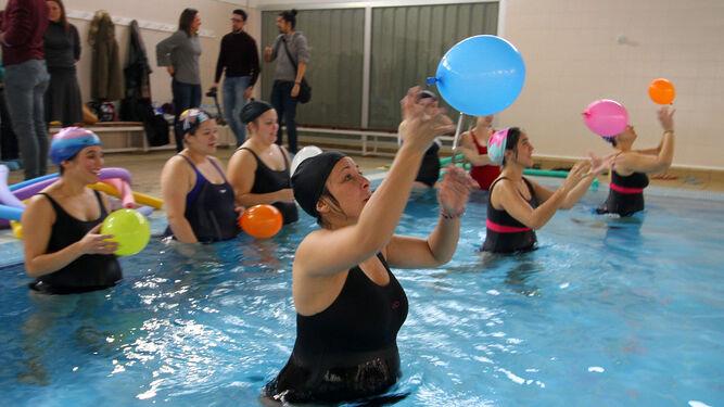 Algunas de las mujeres embarazadas que participan en el curso de preparación al parto realizan uno de los ejercicios con globos en la piscina del Polideportivo Diego Lobato.