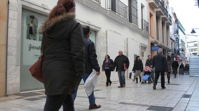 Varias personas caminan por la principal arteria comercial de la capital onubense.