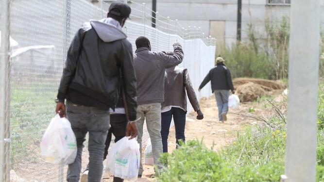 Migrantes subsaharianos cargados con bolsas de víveres.