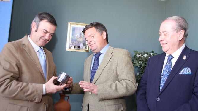 El director de 'Huelva Información' entrega el jarrillo al pregonero en presencia del presidente del Consejo.
