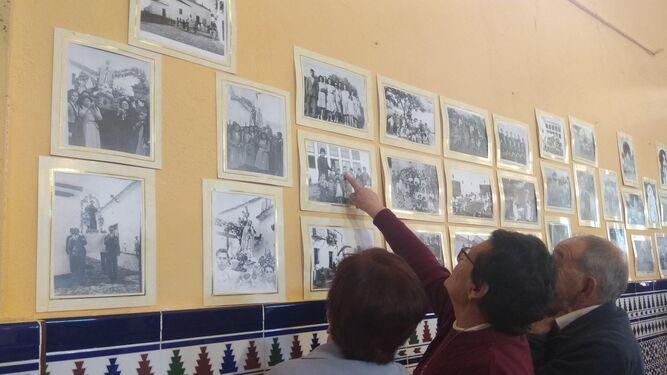 Algunos visitantes miran atentamente la colección de fotografías que incluye la exposición.