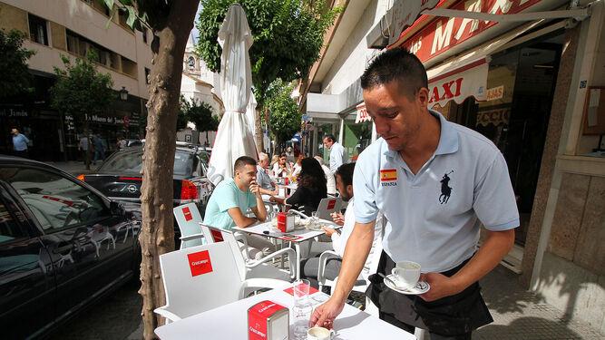 Un camarero recoge una mesa del velador de un establecimiento.