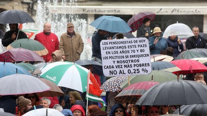 Una pancarta de mensaje elocuente entre los paraguas apostados al final del recorrido en la plaza.