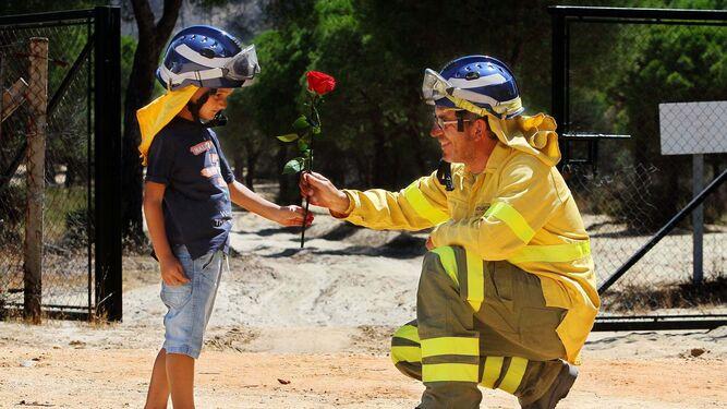 Un niño entrega una rosa a un bombero del Infoca en Mazagón el día siguiente del incendio en el entorno de Doñana.