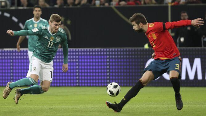 El joven delantero alemán Timo Werner trata de regatear a Gerard Piqué en el partido amistoso disputado ayer en Düsseldorf.
