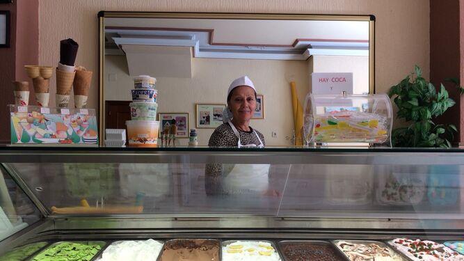 Isabel Grao tras la colorida vitrina de la heladería La Perla, en el Paseo de los Reyes de Isla Cristina.