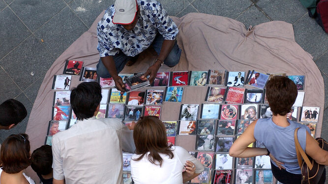 Un mantero ofrece copias de CDs a un grupo de personas en plena calle.