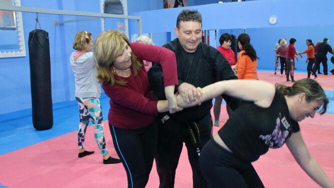 Un monitor muestra a dos mujeres participantes una llave para inmovilizar a un atacante. Debajo, varios momentos del taller en Bollullos.