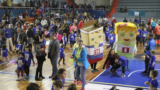 En el centro de la pista, las mascotas del evento interactúan con los menores.