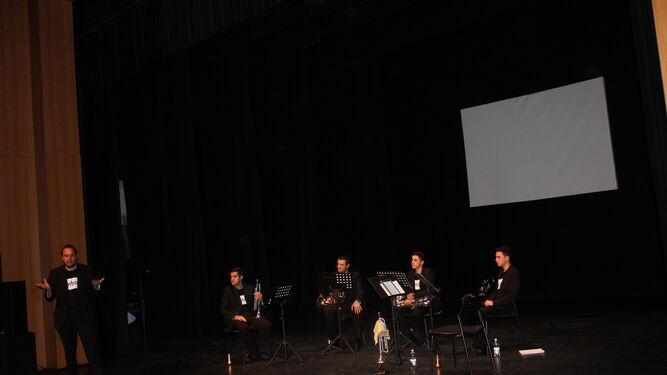 Una de las actuaciones en el Teatro España. Abajo: componentes de Slurbrass y niños del Manuel Siurot haciendo cola para ver el concierto.