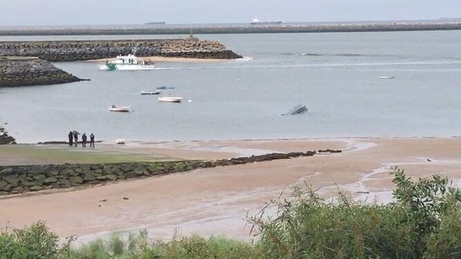 A la derecha, la embarcación semihundida en Mazagón.