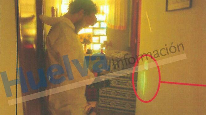 Uno de los agentes del Servicio de Criminalística de la Guardia Civil toma fotografías de una huella encontrada en el pasillo.