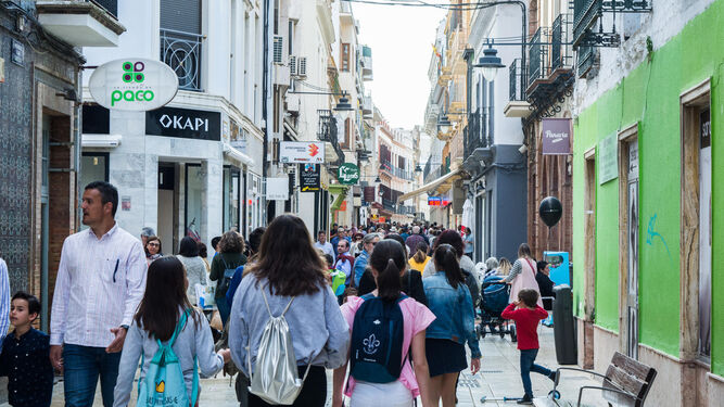 Numerosas personas pasean entre los comercios del centro de Huelva.