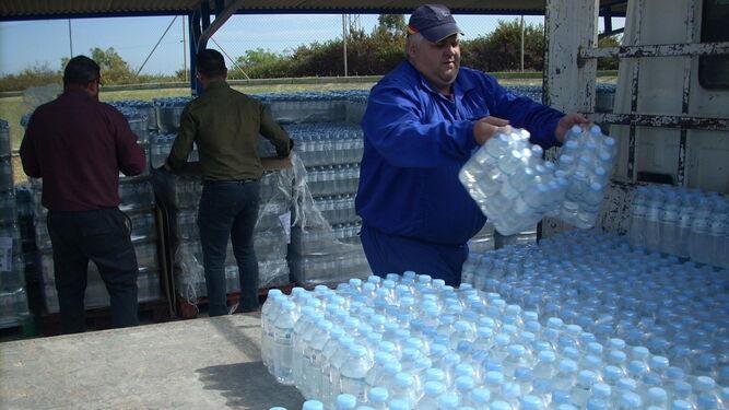 Un operario almacena botellas de agua.
