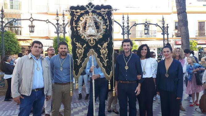 Los hermanos Rodríguez Martín posan con el Simpecado que custodian como hermanos mayores este año.