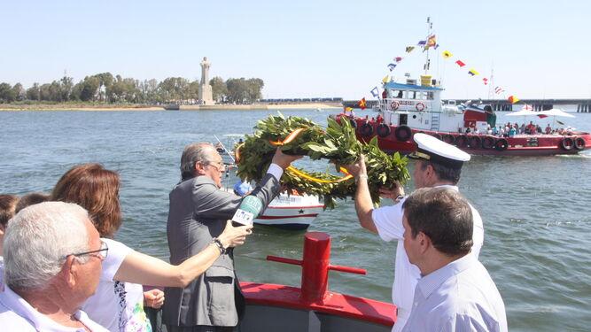 Ofrenda floral en memoria de los fallecidos en el mar durante la procesión de la Virgen del Carmen por la ría de Huelva.