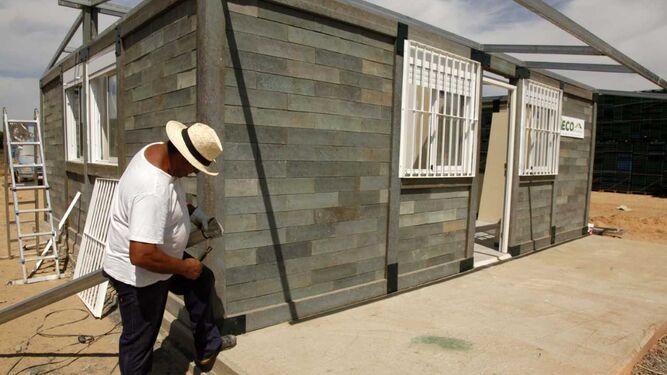 Un operario realiza labores de la edificación de plástico reciclado.
