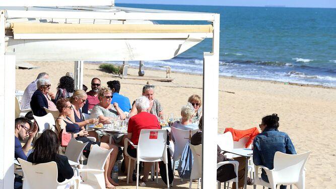 Terraza en la playa con gente tomando el sol y comiendo