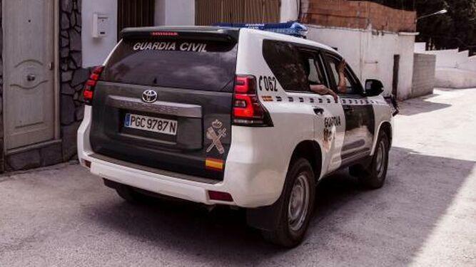 Un coche  de la Guardia  Civil  frente a una vivienda.