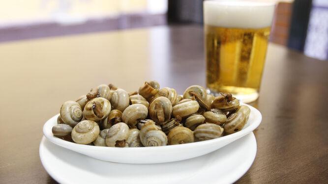 Una cerveza fresquita junto a una tapa de caracoles, combinación ganadora en estas fechas